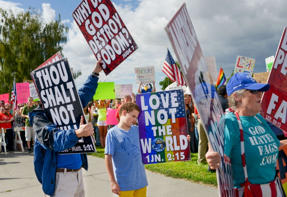 Westboro Baptist Church member Luke Roper, 11, of Topeka, Kansas, stands with his parents Brent, left, and Shirley, right, as they are counter protested by hundreds of supporters of marriage equality in front of Bozeman High School Monday afternoon.