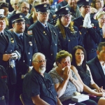 Surrounded by loved ones, Allen and Barbara Rummel, bottom center, parents to Three Forks volunteer fire chief Todd Rummel, react to watching photo slideshow of his life during a memorial service at the Three Forks High School Wednesday afternoon.