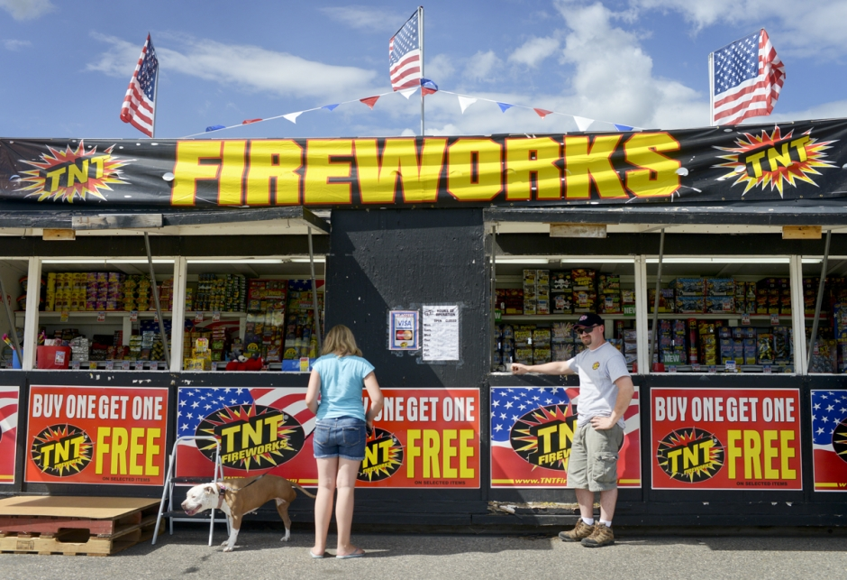 "Alanna Russell, 10, and her red-nosed pitbull ""Nameless"", 5, left, stand in the shade as TNT Fireworks employee Jeff Stacey watches traffic and for his next customer at his fireworks stand along Huffine Lane Monday afternoon."