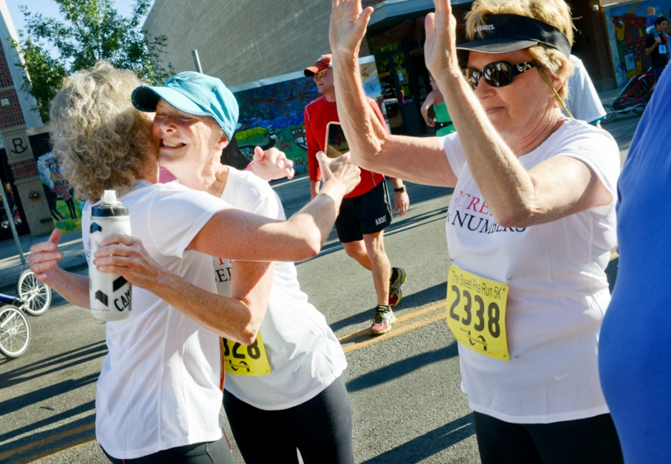 Mike Greener/Chronicle  Cancer survivor Vicki Rich, center, gets hugged by Cancer Support Community executive director Becky Franks, left, as fellow survivor and Power in Numbers running team member Phyllis Wiersma, right, welcomes finishers in the Sweet Pea 5K run Saturday morning in downtown Bozeman.