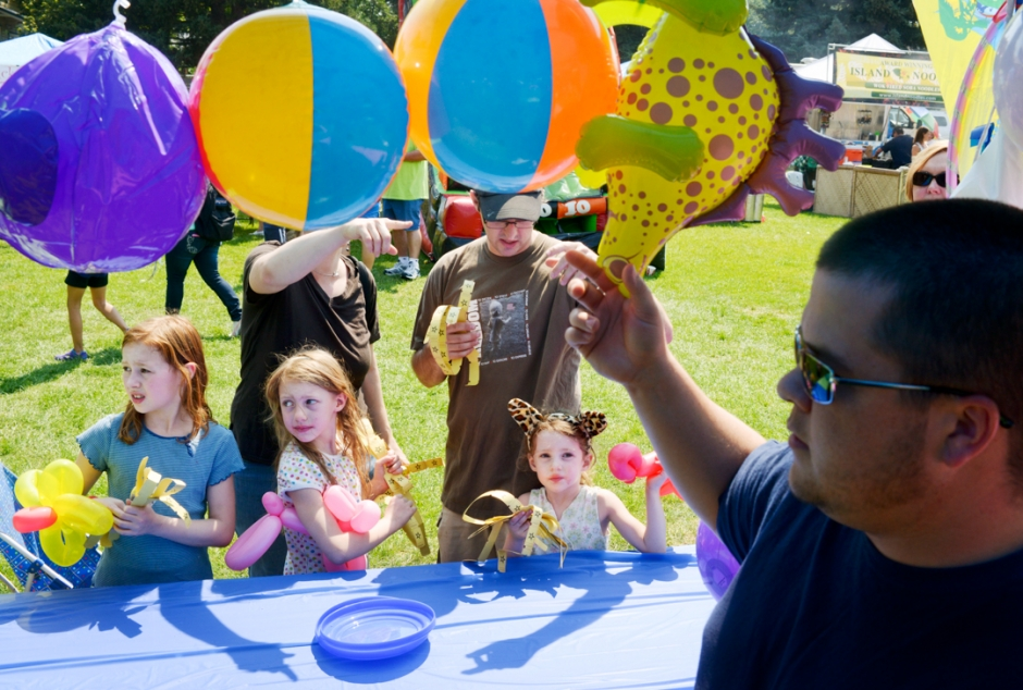 Mike Greener/Chronicle Amber Heinrichs gets advice from her parents Serena and Aubrin on deciding which balloon toy to trade her fair tickets for as her sisters Arianna, 9, and Aaliyah, 7, left, look on during the Agents of Hope Carnival at Bogert Park Saturday afternoon.