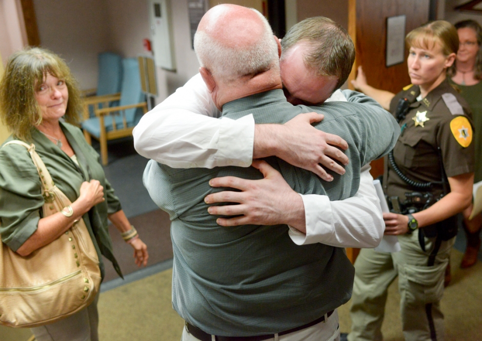 Mike Greener/Chronicle  Jared Kuntz, center, hugs his father Robert V. Kuntz as his mother Kathy, left, looks on after a not guilty verdict was reached in his rape trial Friday afternoon in Bozeman.