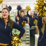 """Mike Greener/Chronicle  Members of the Montana State University cheerleading squad join the Spirit of the West marching band in the isles of ACE Hardware to play school fight songs and create """"Bobcat Buzz"""" in downtown Bozeman Friday morning as part of the 5th Annual MSU Cat Walk."""