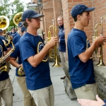 Mike Greener/Chronicle  Montana State University head football coach Rob Ash, center, watches the MSU Spirit of the West marching band during the 5th Annual MSU Cat Walk in downtown Bozeman Friday morning.