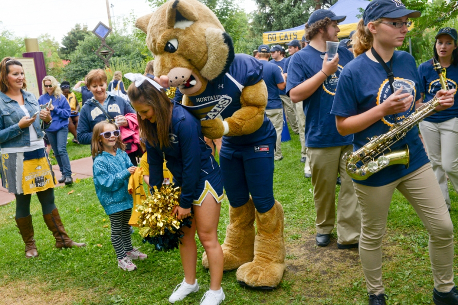 """Mike Greener/Chronicle  Montana State University mascot """"Champ"""" uses the back of a fellow cheerleader to autograph a poster for Carlee Atkinson, 6, center, during the 5th Annual MSU Cat Walk in downtown Bozeman Friday morning."""