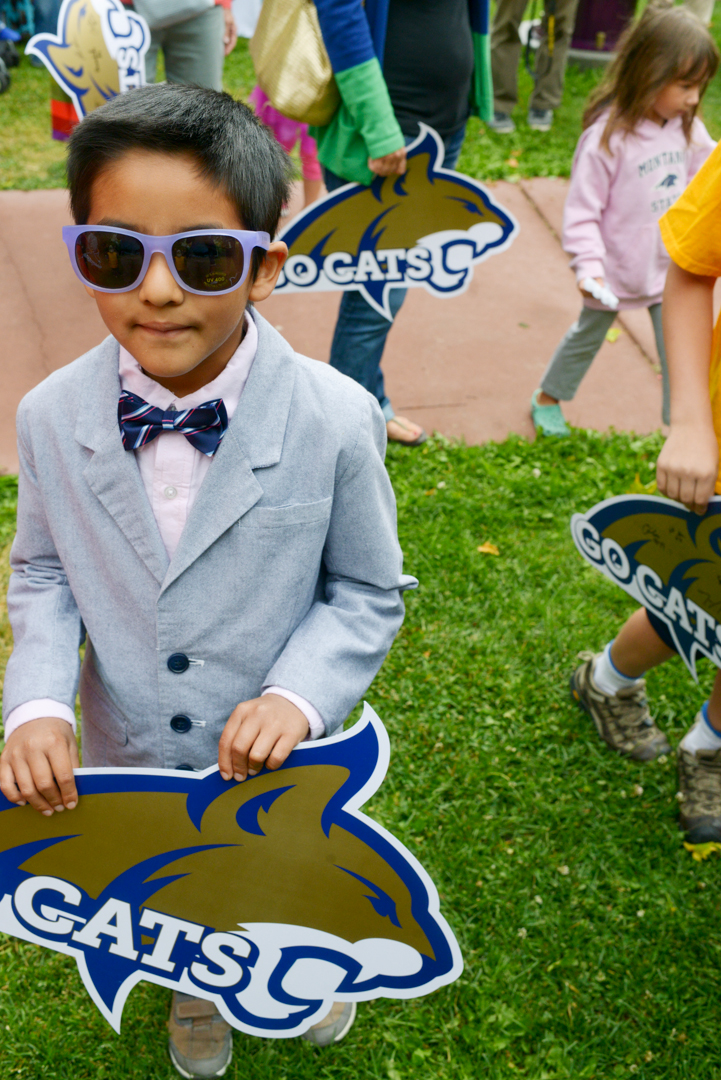 """Mike Greener/Chronicle  Alejandro Rey Shulund, 7, left, waits to have Montana State University mascot """"Champ"""" autograph his poster during the 5th Annual MSU Cat Walk in downtown Bozeman Friday morning."""